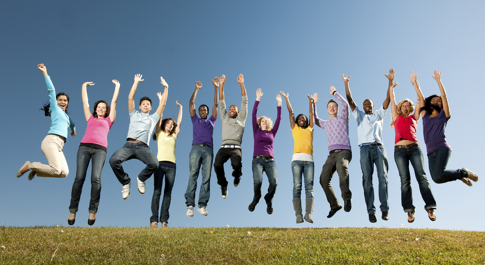 A large group of vibrant young adults outside with a sky backgroun